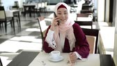 Muslim Woman Talking on Mobile Phone in a Cafe Stok Video