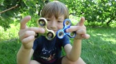 Boy playing with two fidget spinner stress relieving toys outdoor Wideo
