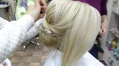 Hairdresser makes evening hairstyle close-up on blond hair of business woman in beauty salon Stok Video