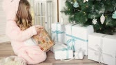 Happy Christmas little girl opening a wrapped Xmas gift box near decorated Christmas tree. Laughing child celebrating Christmas and New Year Winter Holidays. Wideo