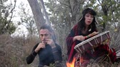 metaphysics : shamanic woman playing on shaman frame drum in the nature around the fire and a man playing a harp