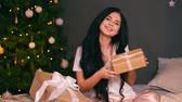 docerias : Portrait of young beautiful woman with decorated tree. New years eve Stock Footage