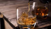 koňak : Golden whiskey pouring in the glass from the bottle. With ice cubes.