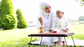 inocente : Muslim family kids and mother relaxing and picnic at park.