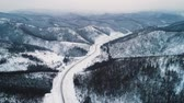 beira da estrada : winter country road in snowy forest, aerial view from drone Stock Footage