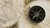 oryantasyon : Disorientated spinning compass against map background closeup footage Stok Video