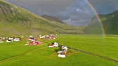 vadi : Gorgeous rainbow over blue ocean waves crashing on stone beach in rural mountain hill village 4k aerial drone landscape