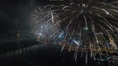 skutečný : Amazing colorful fireworks exploding in dark night sky in bright illumination cityscape skyline background Dostupné videozáznamy