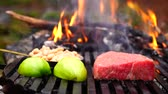 Man hand puts fresh cut vegetables on black grill pan with big piece of beef steak pink meat in forest camp fire flame
