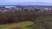 Wonderful aerial 4k drone flight over calm small city cityscape with big mirror surface lake in park on cloudy day