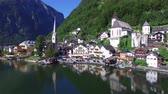 à beira do lago : Beautiful 4k aerial drone panorama flight over small house Austria village in wild nature forest mountain lake landscape Stock Footage