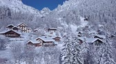 vadi : Impressive aerial drone view on snow covered roof of small cozy luxury villa in winter forest in Alps mountain landscape Stok Video