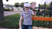 head mounted display : Young man with 3D VR head mounted display in park watching 360 movies, playing VR games.