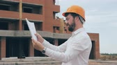 toiler : Chief architect at construction site. Chief architect in a hard hat at construction site looking at the plan, blueprint. Stock Footage