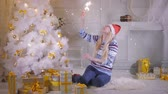 sparkler : Happy smiling woman with new year sparkles laughing and posing near Christmas tree. Stock Footage