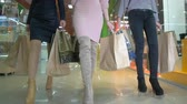 shopaholic : Ladies legs walking in a store. Low shot.