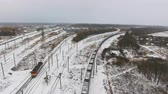 waggon : Freight, cargo train passing railroad station in winter. Aerial shoot. Stock Footage