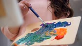cavalete : Female artist mixing colors for her picture.