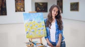 creativeness : Beautiful girl standing next to painted picture. Portrait.