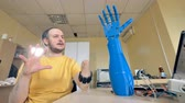 имитация : Male with the amputated arm controls bionic hand. Futuristic concept. 4K. Стоковые видеозаписи