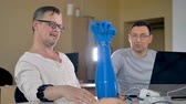 имитация : Mid shot of the two men testing bionic robotic hand. Стоковые видеозаписи