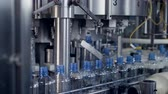 montaj : Bottles transferred from a conveyor to a filling machine.