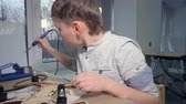 ajustável : A young kid is soldering his modern flying gadget