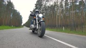wheeled : Someone riding a motorcycle wearing black clothes and helmet.