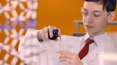 measuring chemicals : A boy scientist counts blue drops falling from a flask into a glass tube. 4K. Stock Footage
