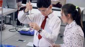 teenage girl : A schoolboy demonstrates how to add chemicals into a tube. Stock Footage