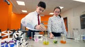 measuring chemicals : A girl watches a boy mixing chemicals. Stock Footage