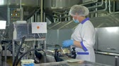 twarożek : A factory operator in a plastic cap and a mask checks cheese packages. 4K. Wideo