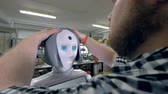 serviceman : An engineer places grey plastic wig on robots head. Stock Footage
