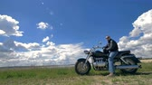 motosiklet : A biker, motorcyclist rest on his motorcycle in a green field under the clouds. 4K. Stok Video
