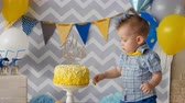 ezmek : A toddler puts a finger inside a birthday cake.