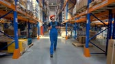 panoya : A worker in a uniform walks along a warehouse corridor.