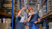 kask : Two warehouse inspectors take inventory together.