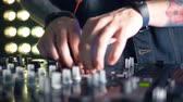 sesleri : Slim DJs hands manipulate mixer console settings.