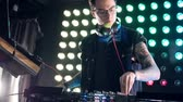 винил : A DJ wearing glasses at a mixer stand.