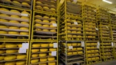 чеддер : Almost completely full storage racks of cheese wheels.
