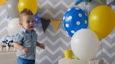 tatarak : A toddler carefully touches colorful balloons. Wideo