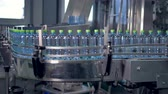 engarrafado : A long factory line with ready unlabeled water bottles.