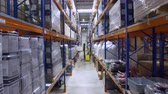 sofőr : Forklift in a warehouse. Modern forklift unloading racks, shelves in storehouse. Aerial.