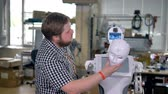 mechanics : An engineer takes off a robots face panel. Stock Footage