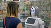 фармацевт : A humanoid robot consults a woman inside a drugstore.