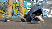 grafiti : A bag full of spray paint bottles falls down on pavement.