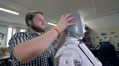 electronics industry : A young engineer checks how robots plastic hair fit. Stock Footage