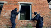 tým : Two armed men aim their guns at an open window.