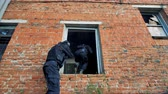 swat : Two soldiers with modern ammunition enter a red brick building through a window.