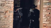 parede de tijolos : Two snipers in black slowly move inside an ancient building during hostages rescuing operation. 4K.